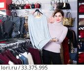 Купить «Adult girl is deciding on warm sweater», фото № 33375995, снято 7 февраля 2017 г. (c) Яков Филимонов / Фотобанк Лори