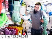 Купить «interested male customer examining climbing equipment in sports equipment store», фото № 33376015, снято 24 февраля 2017 г. (c) Яков Филимонов / Фотобанк Лори