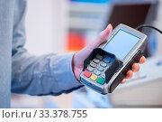 Купить «Shop owner is holding a payment terminal in his hand», фото № 33378755, снято 4 апреля 2020 г. (c) easy Fotostock / Фотобанк Лори