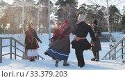 Russian folk - man and woman in Russian folk costumes are dancing traditional dance in sunny weather. Стоковое видео, видеограф Константин Шишкин / Фотобанк Лори