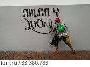 Купить «A radical student of the Universidad Nacional de Colombia paints a political slogan on the wall during a protest march against government's policies and...», фото № 33380783, снято 24 октября 2019 г. (c) age Fotostock / Фотобанк Лори