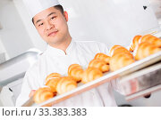 Купить «Young chinese man chelf making bread in kitchen», фото № 33383383, снято 13 июля 2020 г. (c) age Fotostock / Фотобанк Лори