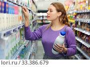 Young positive female customer choosing dairy products in supermarket. Стоковое фото, фотограф Яков Филимонов / Фотобанк Лори