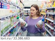 Купить «Young positive female customer choosing dairy products in supermarket», фото № 33386683, снято 31 марта 2020 г. (c) Яков Филимонов / Фотобанк Лори