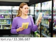 Купить «Young woman choosing sliced cheese at food department in supermarket», фото № 33386687, снято 6 июля 2020 г. (c) Яков Филимонов / Фотобанк Лори
