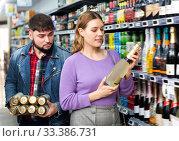 Купить «Young man and woman choosing bottle of cava», фото № 33386731, снято 28 марта 2020 г. (c) Яков Филимонов / Фотобанк Лори