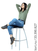 Купить «A young woman in jeans, boots and a khaki shirt is sitting on a high chair. Isolated on white.», фото № 33390827, снято 11 января 2020 г. (c) Serg Zastavkin / Фотобанк Лори