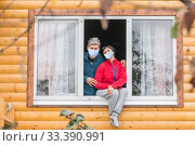 Купить «A lovely mature couple is sitting in a house at the window of medical masks on quarantine and is sadly looking at the nature.», фото № 33390991, снято 29 сентября 2019 г. (c) Акиньшин Владимир / Фотобанк Лори