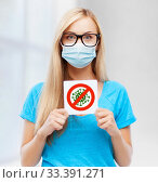 Купить «woman in medical mask holding coronavirus sign», фото № 33391271, снято 30 марта 2013 г. (c) Syda Productions / Фотобанк Лори