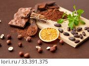 Купить «chocolate with hazelnuts, cocoa beans and orange», фото № 33391375, снято 1 февраля 2019 г. (c) Syda Productions / Фотобанк Лори