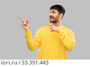 Купить «smiling man pointing fingers to something», фото № 33391443, снято 22 февраля 2020 г. (c) Syda Productions / Фотобанк Лори