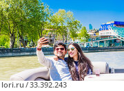 Couple of tourists on Tourist boat cruising on the Kura River in the centre of Tbilisi in Georgia. Редакционное фото, фотограф Николай Коржов / Фотобанк Лори