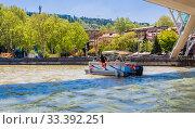 Tourist boat cruising on the Kura River in the centre of Tbilisi in Georgia. Редакционное фото, фотограф Николай Коржов / Фотобанк Лори