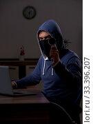 Купить «Male hacker hacking security firewall late in office», фото № 33396207, снято 15 мая 2019 г. (c) Elnur / Фотобанк Лори