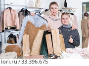 Купить «Satisfied mother and daughter with shopping bags in store», фото № 33396675, снято 21 марта 2018 г. (c) Яков Филимонов / Фотобанк Лори