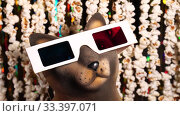 Cat figurine in 3D glasses. Defocused dynamic background of garlands from popcorn and golden sparkling tinsel. Garlands of popcorn for movie news. Invitation to watch movie. 4K video. Стоковое видео, видеограф Dmitry Domashenko / Фотобанк Лори