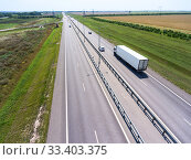 Купить «White semi trailer truck driving on wide straight highway in agricultural fields. View from above. The Don M4 route in Russia», фото № 33403375, снято 30 июля 2018 г. (c) Кекяляйнен Андрей / Фотобанк Лори