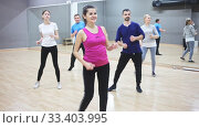 Купить «Smiling dancing people practicing bachata movements in dance studio for adults», видеоролик № 33403995, снято 30 марта 2020 г. (c) Яков Филимонов / Фотобанк Лори