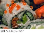Купить «Various kinds of sushi served on dark plate macro», фото № 33407547, снято 11 марта 2020 г. (c) katalinks / Фотобанк Лори