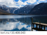 View idyllic Alpine mountains and lake. Focus on wooden pier. Sunny winter morning in Hallstatt, Austria, Europe. Стоковое фото, фотограф Papoyan Irina / Фотобанк Лори