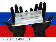 Купить «Doctor holds face mask in hands in black medical gloves on background colors flag of Russia or Russian flag. Pandemic insurance coronavirus», фото № 33408351, снято 6 марта 2020 г. (c) А. А. Пирагис / Фотобанк Лори