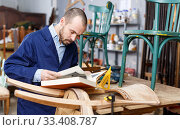 Купить «Portrait of skilled male artisan with book working at vintage furniture repair workshop», фото № 33408787, снято 19 ноября 2018 г. (c) Яков Филимонов / Фотобанк Лори