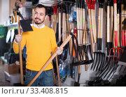 Купить «Man choosing various tools in garden equipment shop», фото № 33408815, снято 2 марта 2017 г. (c) Яков Филимонов / Фотобанк Лори
