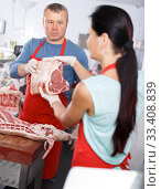 Купить «Positive sellers discussing of quality meat», фото № 33408839, снято 22 июня 2018 г. (c) Яков Филимонов / Фотобанк Лори