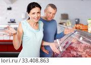 Купить «Sad adult couple customers choosing meat in shop», фото № 33408863, снято 22 июня 2018 г. (c) Яков Филимонов / Фотобанк Лори