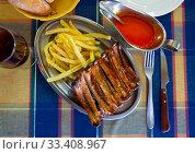 Купить «Grilled pork ribs with french fries, served with tomatoe sause», фото № 33408967, снято 18 июня 2019 г. (c) Яков Филимонов / Фотобанк Лори
