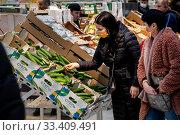 Покупатели выбирают овощи в гипермаркете АШАН в торговом центре Мега в городе Химки во время эпидемии ОРВИ, Московская область, Россия. Редакционное фото, фотограф Николай Винокуров / Фотобанк Лори