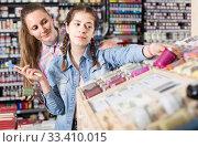 Купить «portrait of mother and daughter choosing paint color in jar in art shop», фото № 33410015, снято 12 апреля 2017 г. (c) Яков Филимонов / Фотобанк Лори