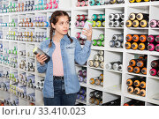 Купить «Portrait of girl choosing paint color in aerosol can in art shop», фото № 33410023, снято 12 апреля 2017 г. (c) Яков Филимонов / Фотобанк Лори
