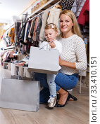 Купить «Mother and daughter with paper bags in clothing shop», фото № 33410151, снято 9 октября 2018 г. (c) Яков Филимонов / Фотобанк Лори