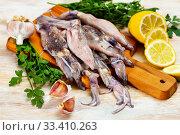 Купить «Uncooked squid with lemon and parsley on a wooden cutting board», фото № 33410263, снято 9 апреля 2020 г. (c) Яков Филимонов / Фотобанк Лори