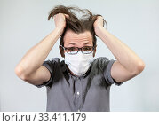 Scared Caucasian man in disposable mask and glasses tears his hair out, male in panic, grey background. Стоковое фото, фотограф Кекяляйнен Андрей / Фотобанк Лори