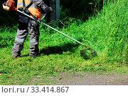 Купить «Worker mowing grass with a trimming machine», фото № 33414867, снято 30 мая 2020 г. (c) easy Fotostock / Фотобанк Лори