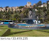 Fountain (El fuente de tres gracias) on the roundabout entering paseo Parque with the Alcazaba in the background - Malaga, Spain. Стоковое фото, фотограф Mehul Patel / age Fotostock / Фотобанк Лори