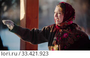 Russian folklore - Russian woman smiling standing outdoors and pointing at something. Стоковое фото, фотограф Константин Шишкин / Фотобанк Лори