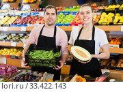 Купить «Young male seller standing with box of green beans and woman with half of melon on the supermarket», фото № 33422143, снято 27 апреля 2019 г. (c) Яков Филимонов / Фотобанк Лори