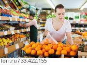 Купить «Adult woman customer choosing fresh oranges», фото № 33422155, снято 27 апреля 2019 г. (c) Яков Филимонов / Фотобанк Лори