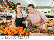 Купить «Young woman wearing apron selling fresh oranges to man customer», фото № 33422159, снято 27 апреля 2019 г. (c) Яков Филимонов / Фотобанк Лори