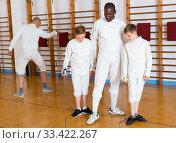 Fencing instructor with young fencers in training room. Стоковое фото, фотограф Яков Филимонов / Фотобанк Лори