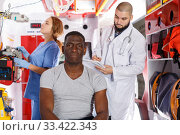 Smiling afro man sitting on stretcher. Стоковое фото, фотограф Яков Филимонов / Фотобанк Лори