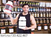 Купить «Positive muscular male seller holding dietary supplements», фото № 33422467, снято 28 марта 2018 г. (c) Яков Филимонов / Фотобанк Лори