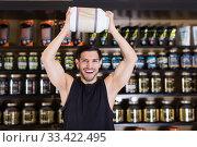 Купить «Sport man holding big pot of sport supplements over head in store», фото № 33422495, снято 28 марта 2018 г. (c) Яков Филимонов / Фотобанк Лори