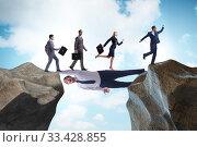 Купить «Businessman acting as a bridge in support concept», фото № 33428855, снято 3 апреля 2020 г. (c) Elnur / Фотобанк Лори