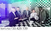 Toned image of businesspeople discussing near chessboard. Стоковое фото, фотограф Яков Филимонов / Фотобанк Лори