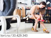 friendly young brunette trying sandals in footwear shop. Стоковое фото, фотограф Яков Филимонов / Фотобанк Лори