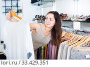 Купить «smiling woman choosing new blouse in apparel shop», фото № 33429351, снято 26 сентября 2016 г. (c) Яков Филимонов / Фотобанк Лори